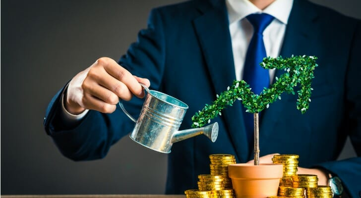 man in a suit watering a plants to show investment